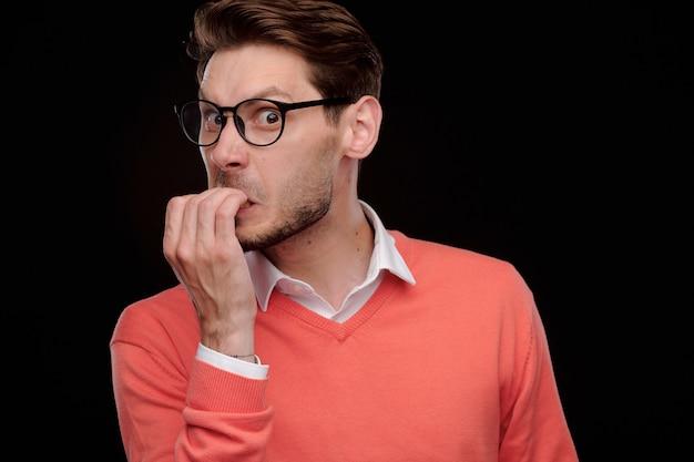 Portret van nerveuze jonge manager in oranje trui vingernagels bijten terwijl paniek