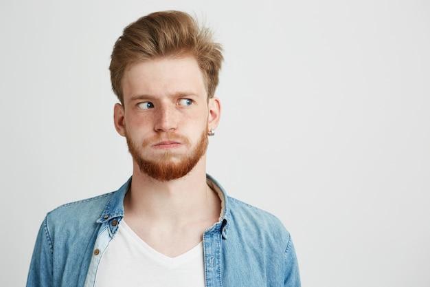 Portret van nerveuze jonge mens met baard die het overhemd van jean draagt dat kant bekijkt.