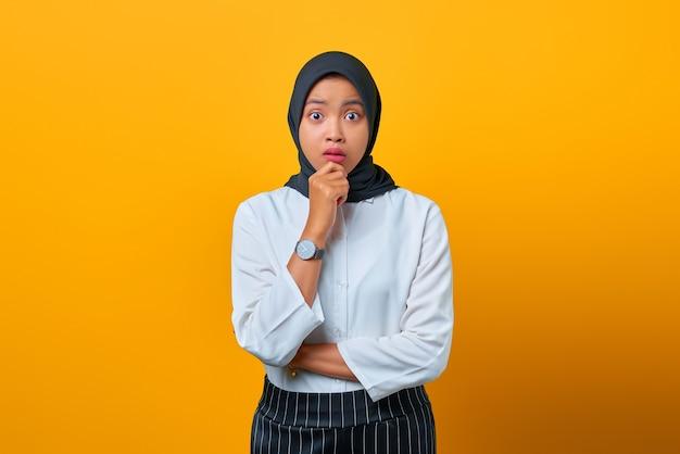 Portret van nerveuze mooie aziatische vrouw ziet er bezorgd uit en hand op lippen op gele achtergrond