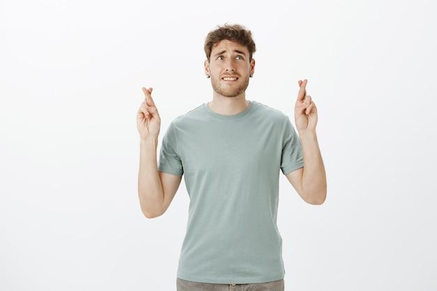 Portret van nerveuze ongeduldige aantrekkelijke man in zwarte oorbellen en t-shirt, gekruiste vingers opheffen, lip bijten en fronsen terwijl hij opkijkt en hoopt dat de wens uitkomt