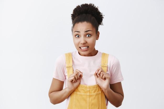 Portret van nerveuze schattige afro-amerikaanse vrouw in gele overall, bukken en balancerende tanden, verontschuldigend en handen wegnemen, staande bezorgd over grijze muur