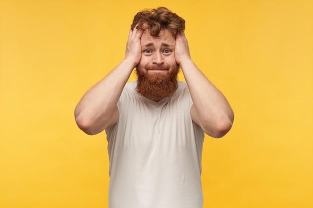 Portret van nerveuze trieste man met rood haar en baard, draagt blanco t-shit, houdt zijn hoofd met beide handen vast