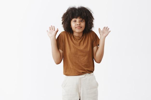 Portret van niet-betrokken kalme en ongeïnteresseerde afro-amerikaanse vrouw met krullend haar schouderophalend met opgeheven handpalmen zonder idee over onderwerp