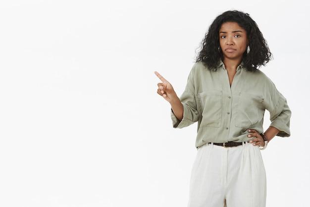 Portret van niet onder de indruk en ontevreden, slim en kieskeurig vrouwtje met een donkere huidskleur