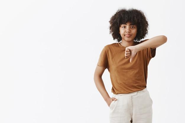 Portret van niet onder de indruk ontevreden snobistische afro-amerikaanse vrouw die moeilijk te imponeren is, grijnzend van teleurstelling met duim omlaag van onverschilligheid en ongenoegen