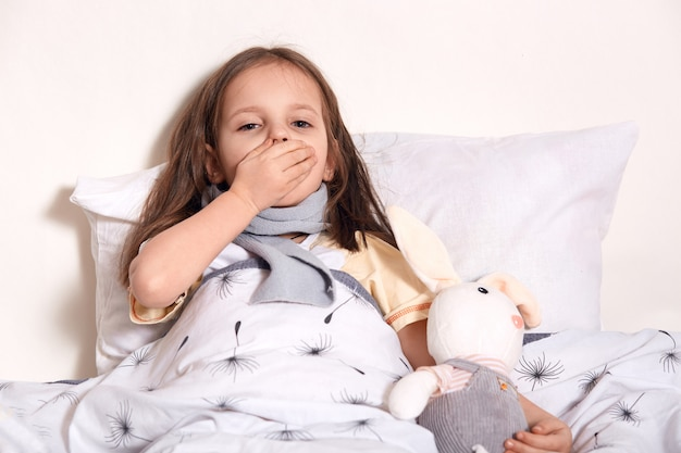Portret van niezend kind, dat haar mond behandelt met hand