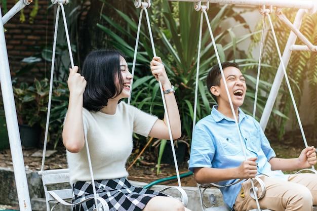Portret van oder zus en jonge broer spelen schommel en lachend samen