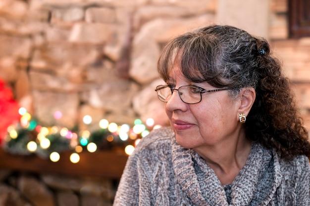 Portret van oma glimlachend en kerstmis thuis vieren op december vakantie