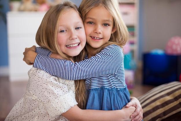 Portret van omhelzende zusters in de woonkamer