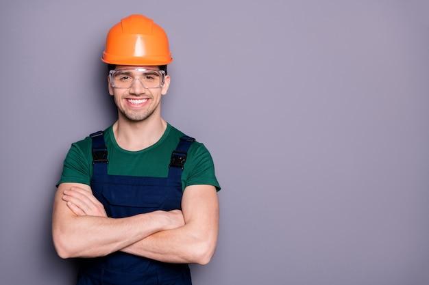 Portret van onafhankelijke reparateur man kruis handen klaar fix appartement muur vernieuwen kamer dragen veiligheidshelm overall groen t-shirt goed kijken uniform geïsoleerd over grijze kleur muur