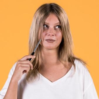 Portret van onbruikbare nadenkende jonge vrouw voor gele achtergrond
