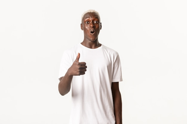 Portret van onder de indruk afro-amerikaanse blonde man, glimlachend verbaasd en duim-omhoog in goedkeuring, als iets