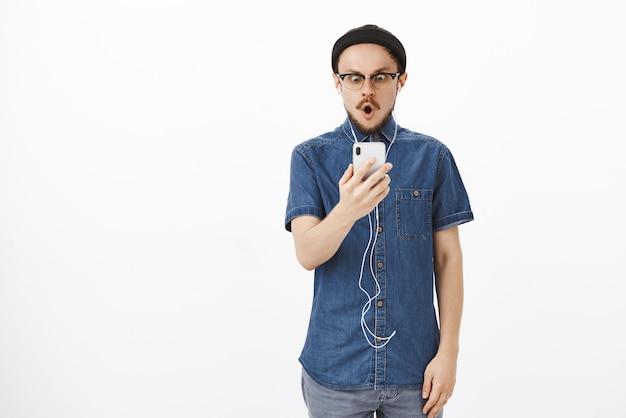 Portret van onder de indruk en verbaasd verbaasd knappe volwassen man met baard in bril en muts vouwende lippen in omg of wow starend naar smartphonescherm onder de indruk en verrast met oortelefoons