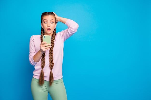 Portret van onder de indruk gefrustreerd duizendjarig meisje met lange staartjes krijgen sociale media blog post commentaar kijken mobiel voelen nerveus aanraken hoofd schreeuwen dragen stijlvolle outfit geïsoleerde blauwe kleur achtergrond