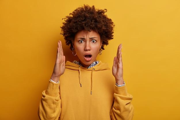 Portret van onder de indruk geschokte vrouw maakt groot formaat gebaar