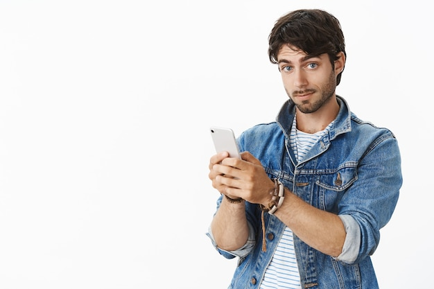 Portret van onder de indruk knappe europese man met borstelharen en blauwe ogen in trendy spijkerjasje met smartphone die wenkbrauwen opheft en tevreden naar voren staart
