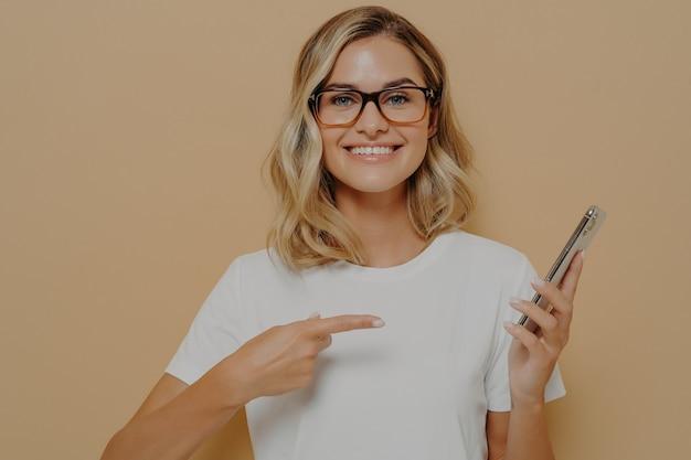 Portret van onder de indruk, opgewonden jonge blonde vrouw die iets geweldigs laat zien, wijzend op het scherm van de mobiele telefoon met wijsvinger en breed lachend, opscheppen met haar recente overwinning op casino-app