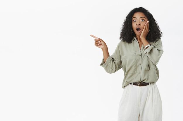 Portret van onder de indruk sprakeloze en verbaasde jonge donkere vrouwelijke fan in stijlvolle blouse met krullend haar en zegt wow