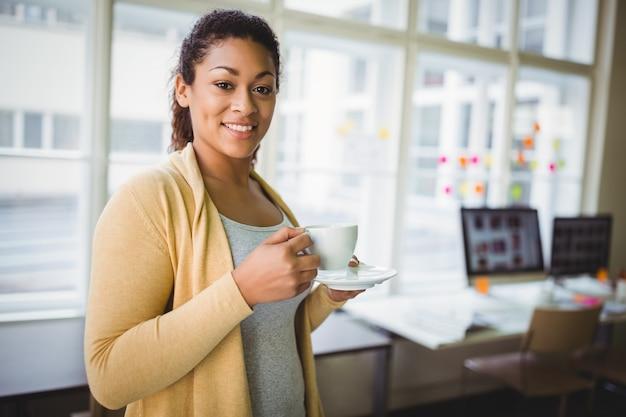Portret van onderneemster die koffie in creatief bureau hebben