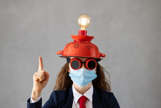 Portret van onderneemster die medisch beschermend masker draagt tegen grijze concrete muur. zakendoen tijdens coronavirus covid-19 pandemie concept