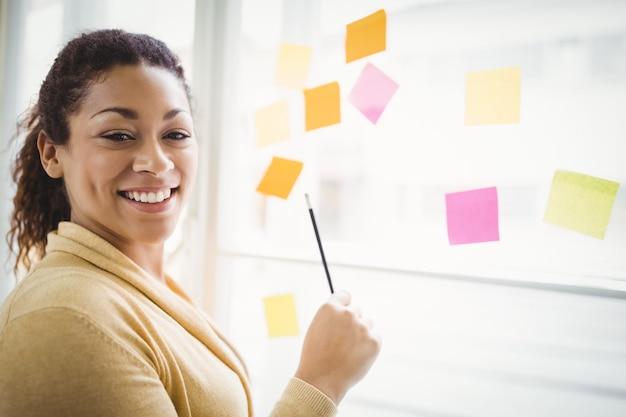 Portret van onderneemster die op zelfklevende nota's in creatief bureau schrijven