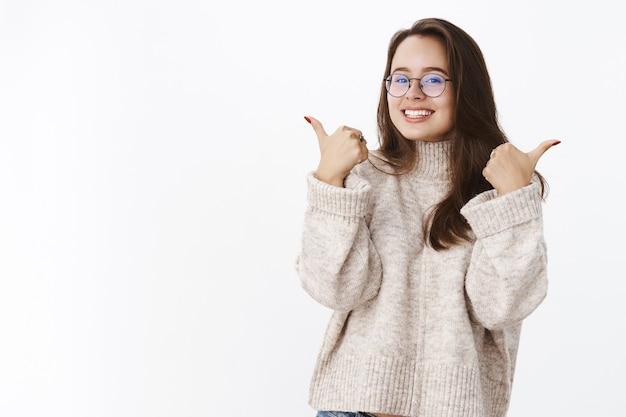 Portret van ondersteunende tevreden en opgetogen vrouwelijke klant in trui en bril die duimen omhoog geeft
