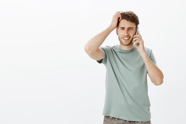 Portret van ondervraagde schattige blonde man met borstelharen, smartphone in de buurt van oor houden en hoofd krabben terwijl hij de vraag probeert te beantwoorden, onzeker en twijfelachtig is