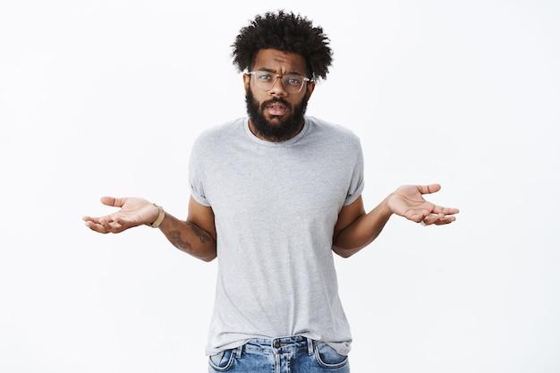 Portret van ongehinderde, onverschillige zelfverzekerde afro-amerikaanse man met baard en krullend haar schouderophalend met handen zijwaarts gespreid in ongeïnteresseerde en onzorgvuldige pose over grijze muur