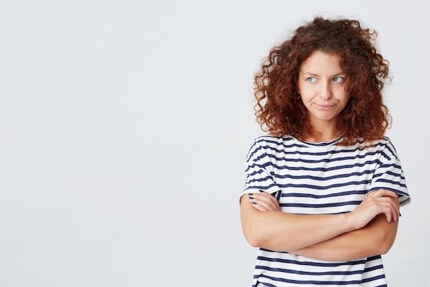 Portret van ongelukkig droevig krullend jonge vrouw draagt gestreepte t-shirt kijkt naar de zijkant