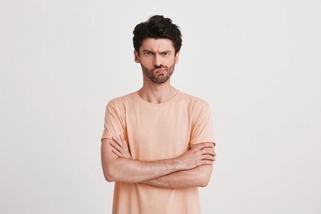 Portret van ongelukkig ontevreden jongeman met borstelharen draagt perzik t-shirt kijkt boos en wijst naar de kant met vinger geïsoleerd op wit