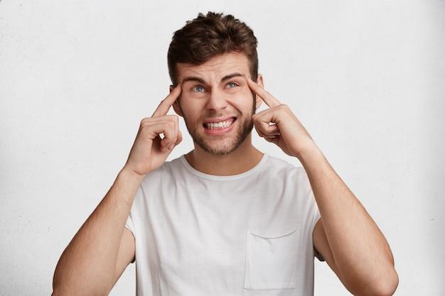 Portret van ongelukkig stressvolle ongeschoren man draagt wit t-shirt, houdt vingers op slapen, klemt tanden, geïsoleerd op studio achtergrond. ontevreden jonge bebaarde man drukt negatieve emoties uit