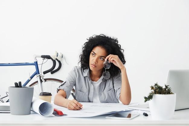 Portret van ongelukkige en vermoeide jonge afro-amerikaanse vrouwelijke architect die aan blauwdrukken werkt