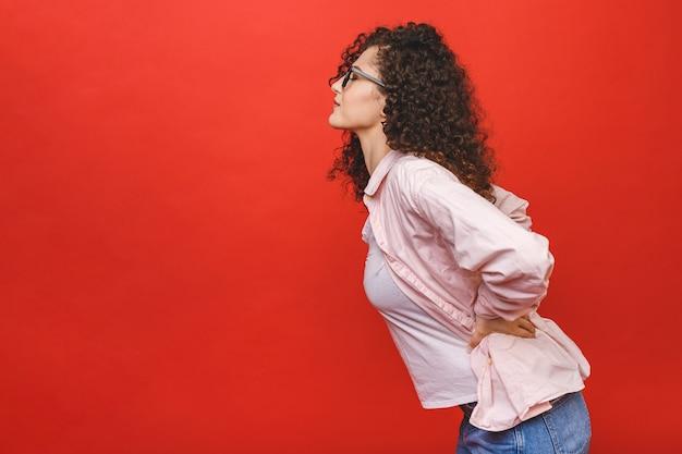 Portret van ongelukkige jonge studentenvrouw die aan rugpijn lijdt die over rode achtergrond wordt geïsoleerd.