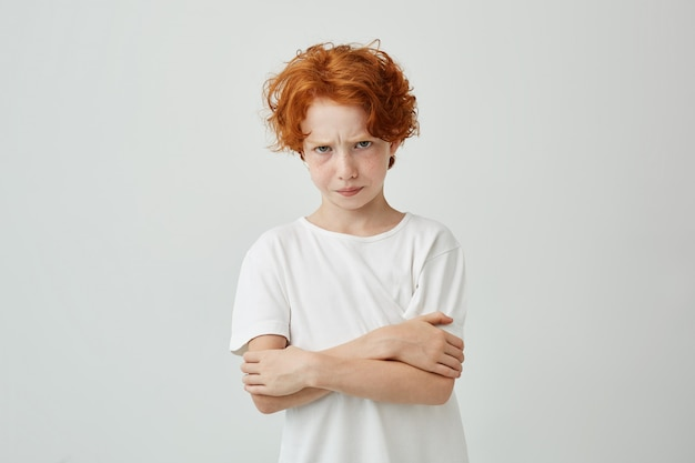 Portret van ongelukkige roodharige jongen met sproeten op zoek met verstoorde uitdrukking, gekruiste handen ontevreden dat zijn moeder hem uitschold.