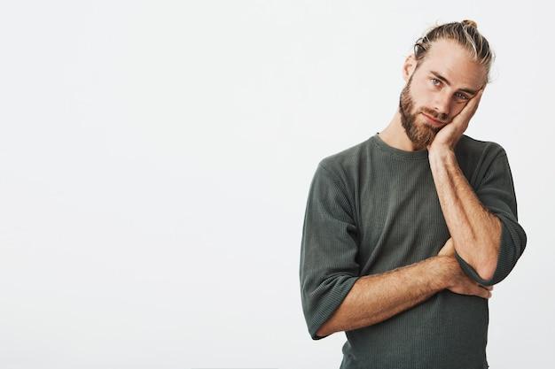 Portret van ongelukkige volwassen bebaarde man in grijs shirt met hand op uitgeput en moe wang