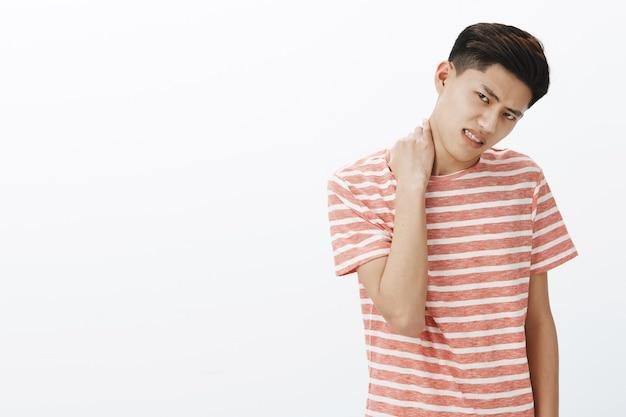 Portret van ongemakkelijke jonge aziatische man in gestreept t-shirt die niet bereid is iets te doen, nek kantelend hoofd wrijven en fronsen ongenoegen uiten