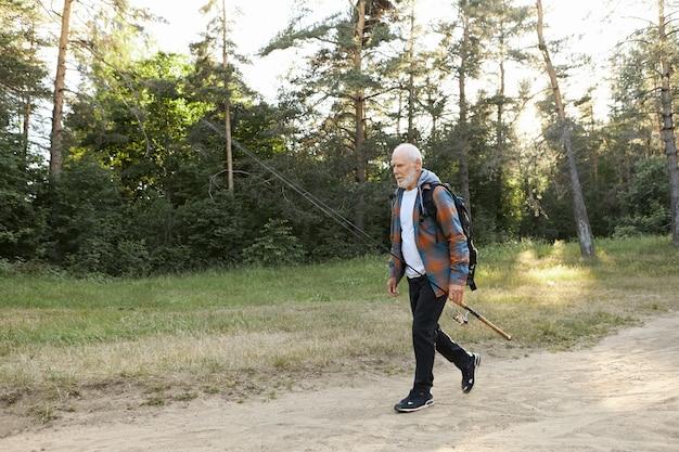 Portret van ongeschoren kale europese mannelijke gepensioneerde met rugzak, visserijhengel of draaiende haspel, die vis gaat vangen op de rivieroever. recreatievisserij, actieve gezonde levensstijl en vrije tijd