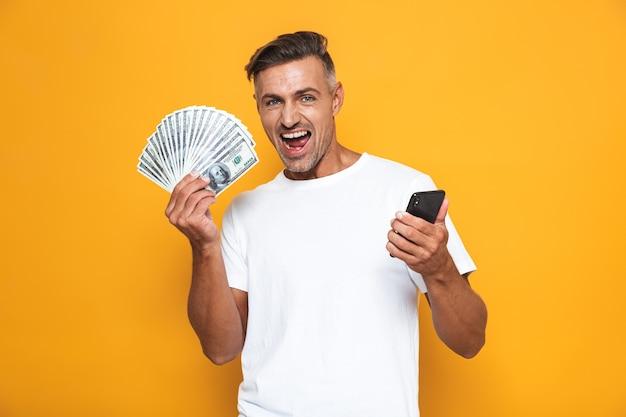 Portret van ongeschoren man 30s in wit t-shirt met mobiele telefoon en een hoop geld geïsoleerd op geel