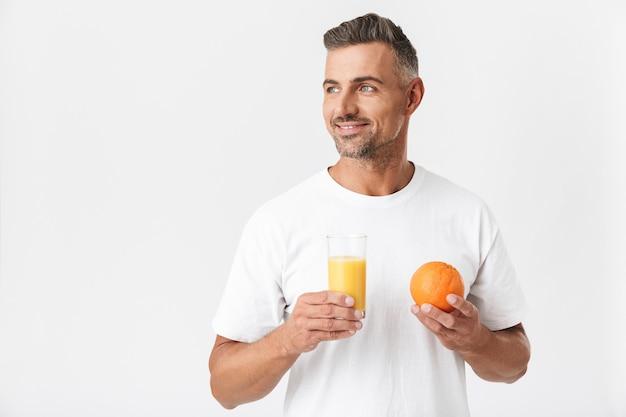 Portret van ongeschoren man 30s met borstelharen dragen casual t-shirt met glas sap en oranje fruit geïsoleerd op wit