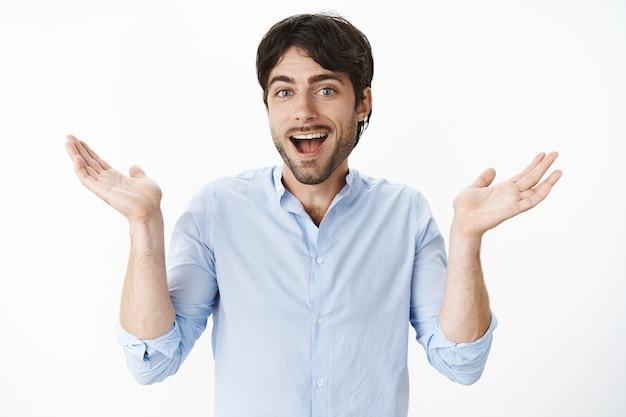 Portret van ongestoorde en zorgeloze kilte en gelukkige jonge knappe vrolijke man met blauwe ogen en baard schouderophalend met opgeheven handen en zijwaarts gespreid glimlachend tevreden