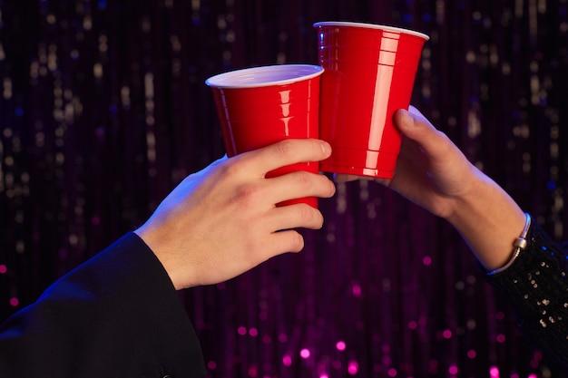 Portret van onherkenbaar koppel rammelende redplastic bekers close-up terwijl het drinken van alcohol op feestje, kopieer ruimte