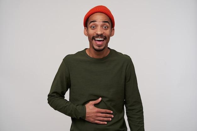 Portret van onjoyed jonge, bebaarde donkere man met grote ogen geopend en hand op zijn buik terwijl hij gelukkig lacht, geïsoleerd op wit