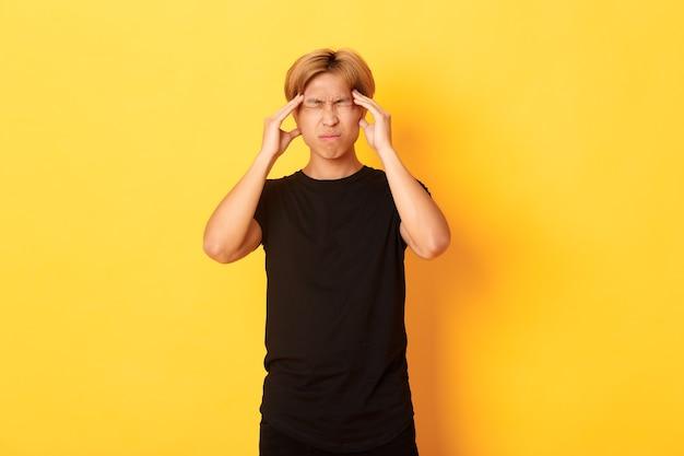 Portret van onrustige aziatische mannelijke student met hoofdpijn, grimassen van pijn en hoofd aan te raken, migraine lijden.