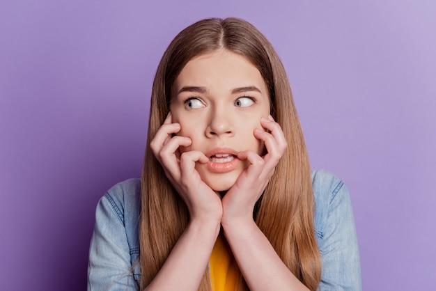 Portret van onrustige, nerveuze dame die vingers bijt, kijk naar de lege ruimte en draag jeanskleding op een paarse achtergrond