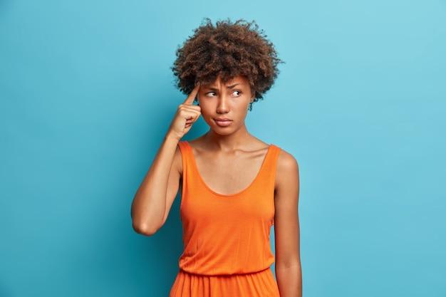 Portret van onrustige ontevreden mooie jonge afro-amerikaanse vrouw houdt vinger op haar tempel