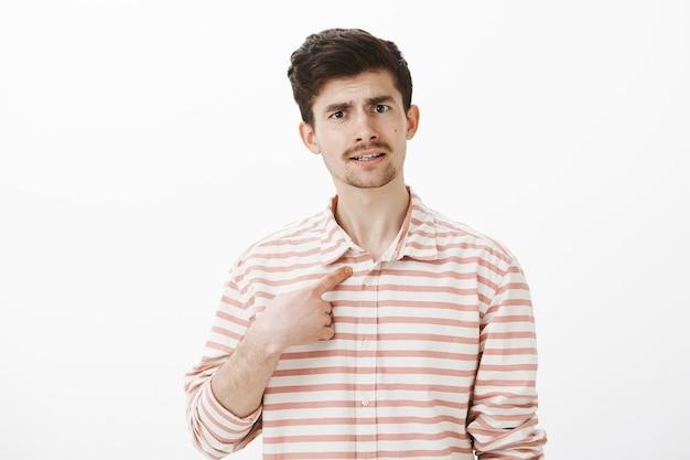 Portret van ontevreden aantrekkelijke man met snor, wijzend naar zichzelf met wijsvinger, wenkbrauwen optillen van verbazing, ruzie, beschuldigd van slechte dingen doen, gefrustreerd over grijze muur