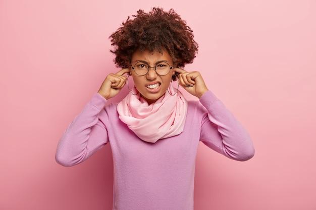 Portret van ontevreden afro-amerikaanse vrouw sluit oren en grijnst gezicht, vermijdt hard geluid, draagt een transparante bril, casual paarse slijtage