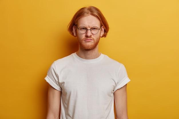 Portret van ontevreden bebaarde gember man grijnst gezicht