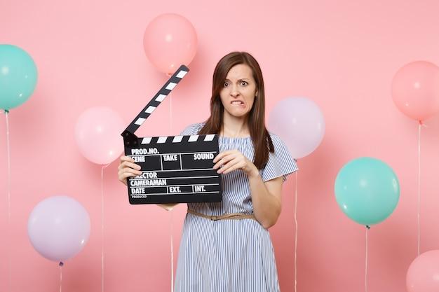 Portret van ontevreden bezorgde vrouw in blauwe jurk die lippen bijt met klassieke zwarte film filmklapper op pastelroze achtergrond met kleurrijke luchtballonnen. verjaardagsfeestje concept.