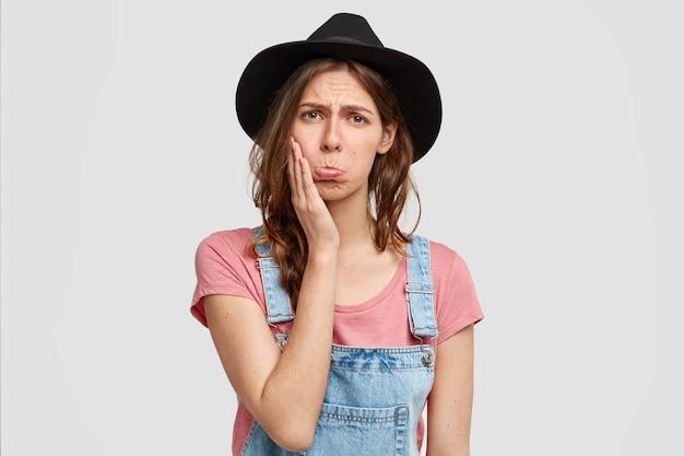Portret van ontevreden boerin die in een lage geest is vanwege slechte weersomstandigheden, portemonnees lippen, casual overall en hoed draagt